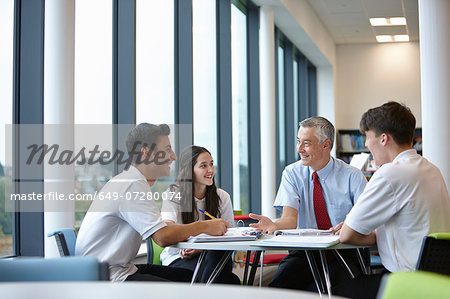 Group of teenagers working with teacher in school class Stock Photo - Premium Royalty-Free, Image code: 649-07280074