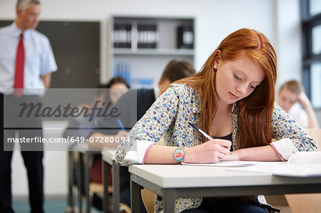 Teacher watching over teenagers in classroom Stock Photo - Premium Royalty-Free, Image code: 649-07280094