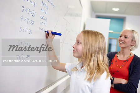 Schoolgirl doing multiplication on white board Stock Photo - Premium Royalty-Free, Image code: 649-07280099
