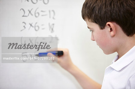 Close up of schoolboy doing multiplication on white board Stock Photo - Premium Royalty-Free, Image code: 649-07280102