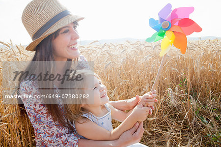 Mother and daughter in wheat field holding windmill Stock Photo - Premium Royalty-Free, Image code: 649-07280282