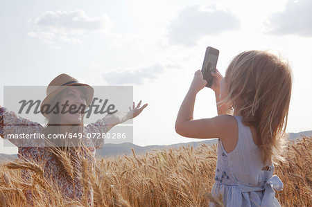 Girl taking photograph of mother in wheat field with arms open Stock Photo - Premium Royalty-Free, Image code: 649-07280286