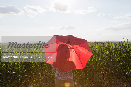 Woman standing holding red umbrella Stock Photo - Premium Royalty-Free, Image code: 649-07280317