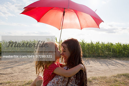 Mother and daughter hugging under red umbrella Stock Photo - Premium Royalty-Free, Image code: 649-07280321