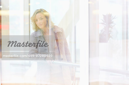 Mid adult woman peering through shopping centre window Stock Photo - Premium Royalty-Free, Image code: 649-07280400