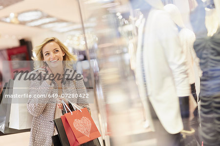Mid adult female shopper carrying bags in shopping centre Stock Photo - Premium Royalty-Free, Image code: 649-07280422