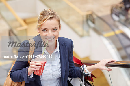 Businesswoman on escalator with shopping and fruit drink Stock Photo - Premium Royalty-Free, Image code: 649-07280428