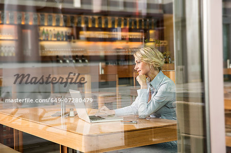 Businesswoman using laptop, view through window Stock Photo - Premium Royalty-Free, Image code: 649-07280479
