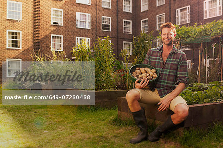 Mid adult man on council estate allotment with bowl of potatoes Stock Photo - Premium Royalty-Free, Image code: 649-07280488