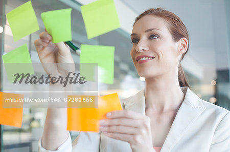Businesswoman brainstorming using sticky notes Stock Photo - Premium Royalty-Free, Image code: 649-07280666