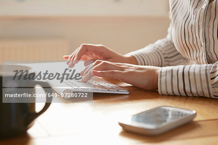 Cropped image of woman typing on wireless keyboard Stock Photo - Premium Royalty-Free, Image code: 649-07280722
