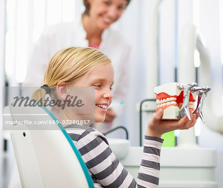 Girl in dentists chair holding false teeth Stock Photo - Premium Royalty-Free, Image code: 649-07280857