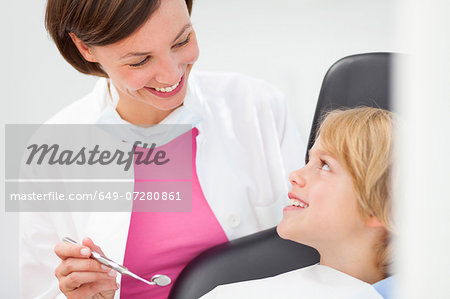 Boy having check up, dentist holding dental mirror Stock Photo - Premium Royalty-Free, Image code: 649-07280861