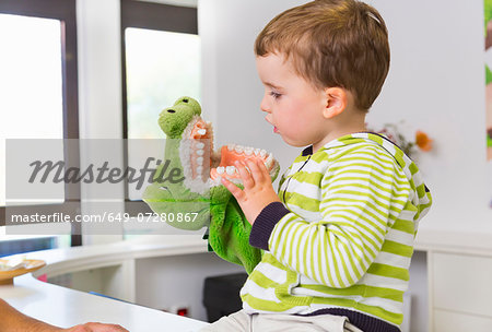Boy playing with toy crocodile in dentists Stock Photo - Premium Royalty-Free, Image code: 649-07280867