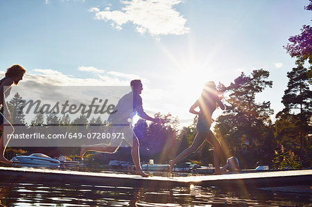 Three adult friends running along pier, Gavle, Sweden Stock Photo - Premium Royalty-Free, Image code: 649-07280971