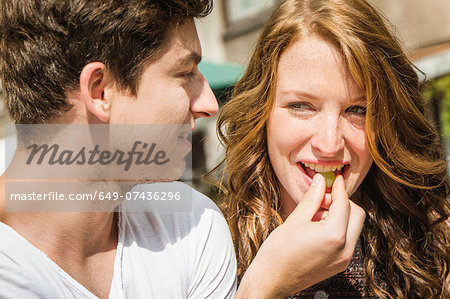 Young couple eating grapes Stock Photo - Premium Royalty-Free, Image code: 649-07436296