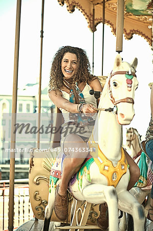 Young woman riding carousel Stock Photo - Premium Royalty-Free, Image code: 649-07436334