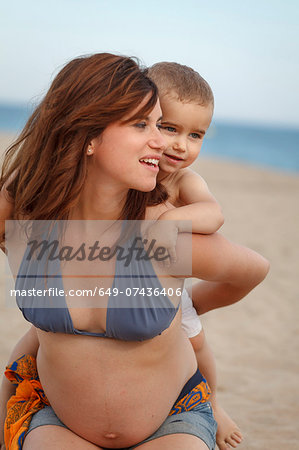 Pregnant mother giving toddler piggy back Stock Photo - Premium Royalty-Free, Image code: 649-07436406
