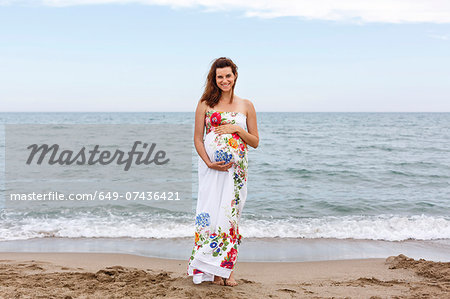 Pregnant woman standing on beach, hands on stomach Stock Photo - Premium Royalty-Free, Image code: 649-07436421