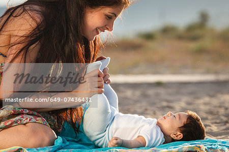 Mother looking down at baby lying on rug Stock Photo - Premium Royalty-Free, Image code: 649-07436431