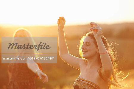 Woman and teenager dancing in field at dusk Stock Photo - Premium Royalty-Free, Image code: 649-07436497