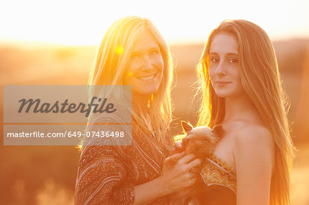 Woman and teenager standing in field at dusk holding domestic dog Stock Photo - Premium Royalty-Free, Image code: 649-07436498