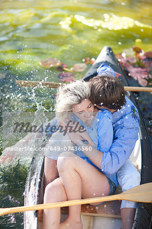 Young romantic couple fooling around in rowing boat Stock Photo - Premium Royalty-Free, Image code: 649-07436560