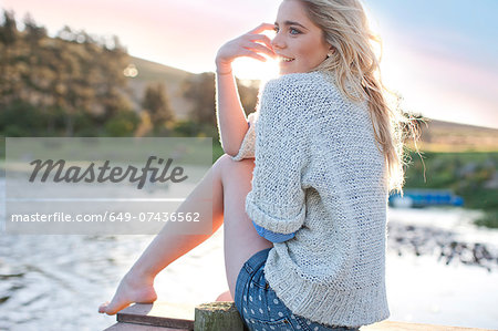 Young woman sitting on pier Stock Photo - Premium Royalty-Free, Image code: 649-07436562
