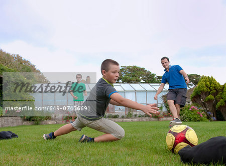 Father and sons playing football in garden Stock Photo - Premium Royalty-Free, Image code: 649-07436691