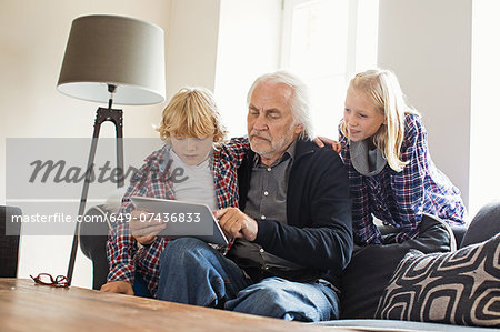 Grandfather using digital tablet with grandchildren Stock Photo - Premium Royalty-Free, Image code: 649-07436833