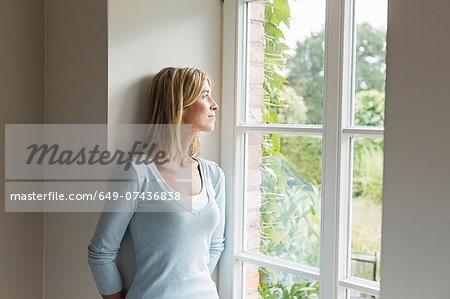 Portrait of mid adult woman looking out of window