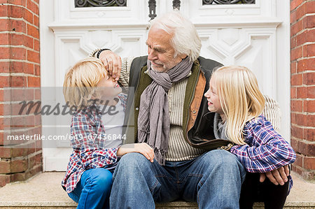 Grandfather sitting with grandchildren on front doorstep Stock Photo - Premium Royalty-Free, Image code: 649-07436844