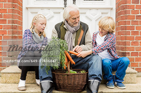 Grandfather sitting with grandchildren on doorstep with carrots Stock Photo - Premium Royalty-Free, Image code: 649-07436847