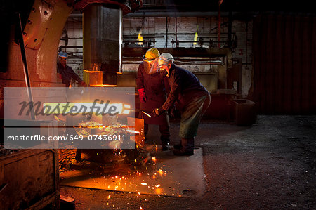 Forge workers pre form red hot billet into flight bar (mining component) on hammer Stock Photo - Premium Royalty-Free, Image code: 649-07436911