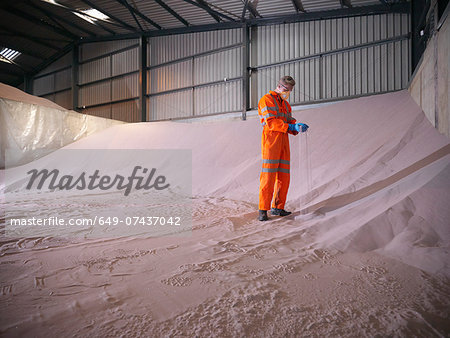 Worker in reflective clothing inspecting zircon sand Stock Photo - Premium Royalty-Free, Image code: 649-07437042