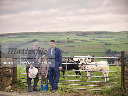 Mature farmer, adult son and grandson standing together at gate to cow field, portrait Stock Photo - Premium Royalty-Free, Image code: 649-07437076
