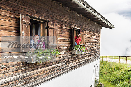 Portrait of family at chalet windows, Achenkirch,  Tyrol, Austria Stock Photo - Premium Royalty-Free, Image code: 649-07437142