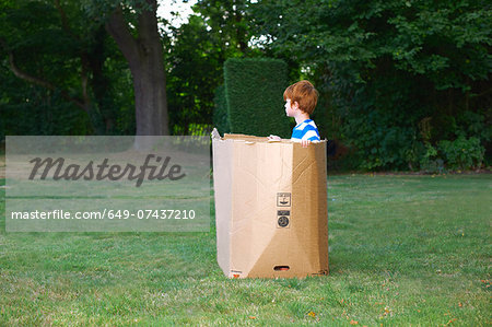 Young boy watching from cardboard box in garden Stock Photo - Premium Royalty-Free, Image code: 649-07437210