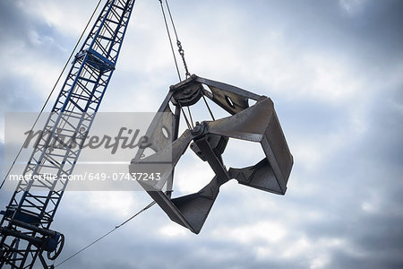 Low angle view of crane grab against cloudy sky Stock Photo - Premium Royalty-Free, Image code: 649-07437243