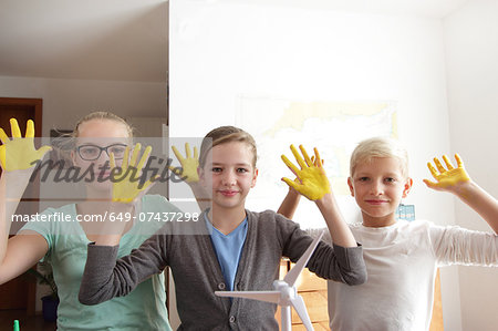 Two sisters and brother with yellow sunshine hands and a model of wind turbine Stock Photo - Premium Royalty-Free, Image code: 649-07437298