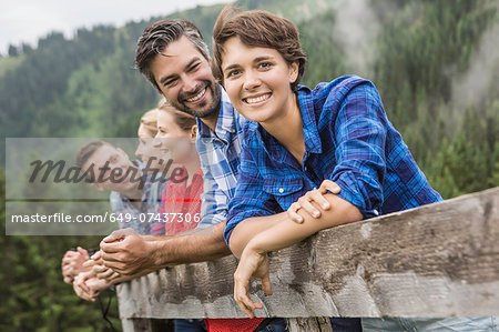 Group of friends leaning on wooden fence, Tirol, Austria Stock Photo - Premium Royalty-Free, Image code: 649-07437306