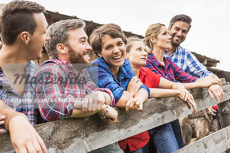 Group of friends leaning on wooden fence, Tirol, Austria Stock Photo - Premium Royalty-Free, Image code: 649-07437308