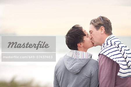 Gay couple kissing on beach Stock Photo - Premium Royalty-Free, Image code: 649-07437403