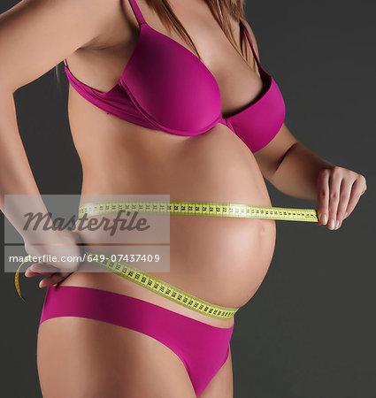 Pregnant woman measuring belly Stock Photo - Premium Royalty-Free, Image code: 649-07437409