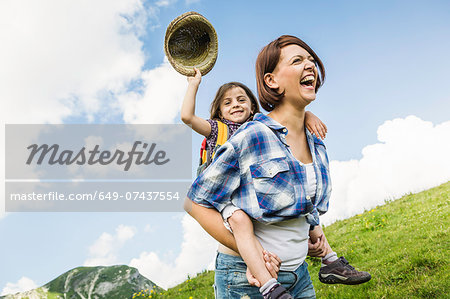 Mother and daughter on hike, girl holding straw hat Stock Photo - Premium Royalty-Free, Image code: 649-07437554