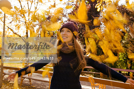 Young woman throwing up autumn leaves in park Stock Photo - Premium Royalty-Free, Image code: 649-07437633