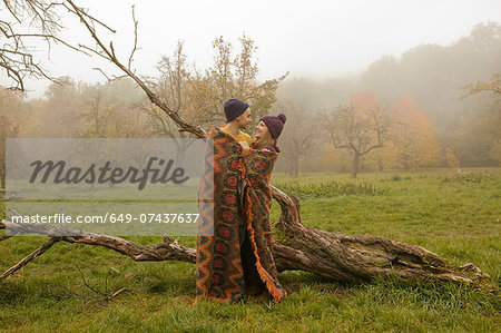 Young couple wrapped in blanket in misty park Stock Photo - Premium Royalty-Free, Image code: 649-07437637