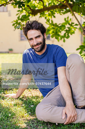 Portrait of mid adult man sitting on grass Stock Photo - Premium Royalty-Free, Image code: 649-07437644
