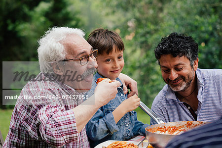 Senior man enjoying food with grandson and son Stock Photo - Premium Royalty-Free, Image code: 649-07437658