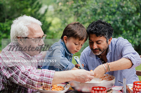 Three generations of male family enjoying a meal together Stock Photo - Premium Royalty-Free, Image code: 649-07437659